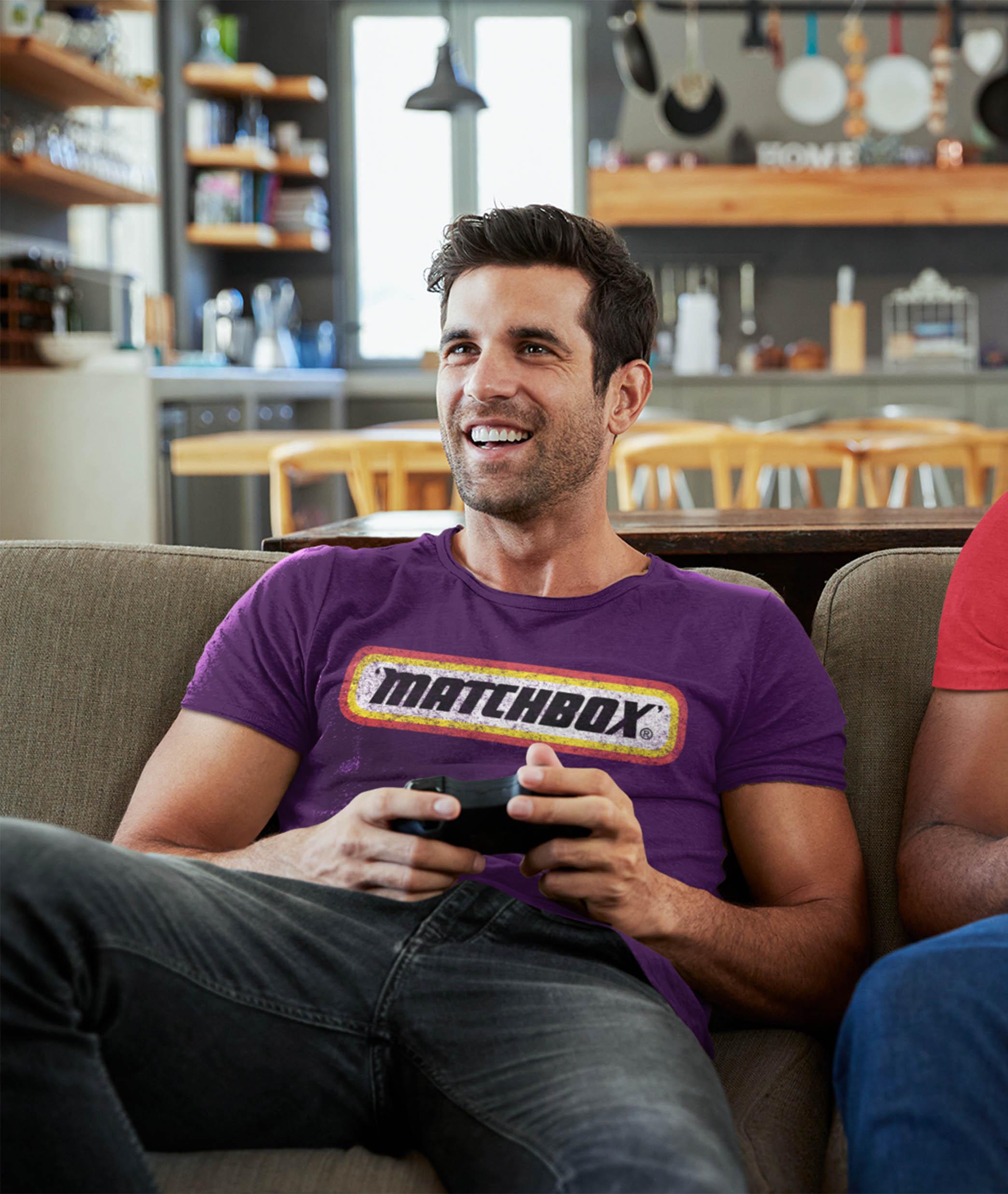Man wearing purple Matchbox t-shirt playing computer game