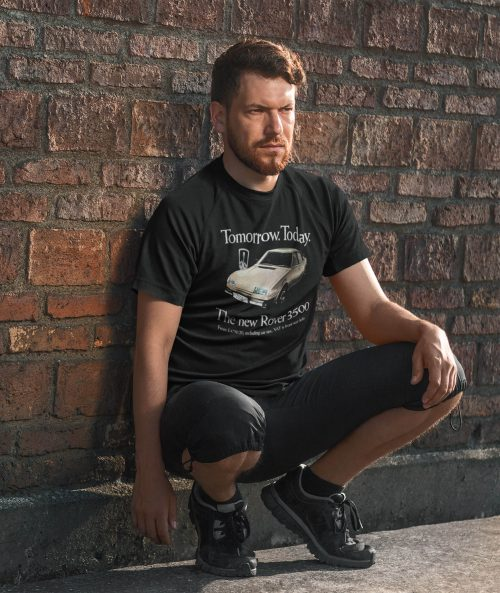 Man leaning on a wall wearing a black Rover 3500 SD1 t shirt