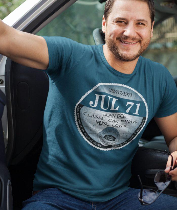 Man in car wearing indigo large tax disc graphic t shirt