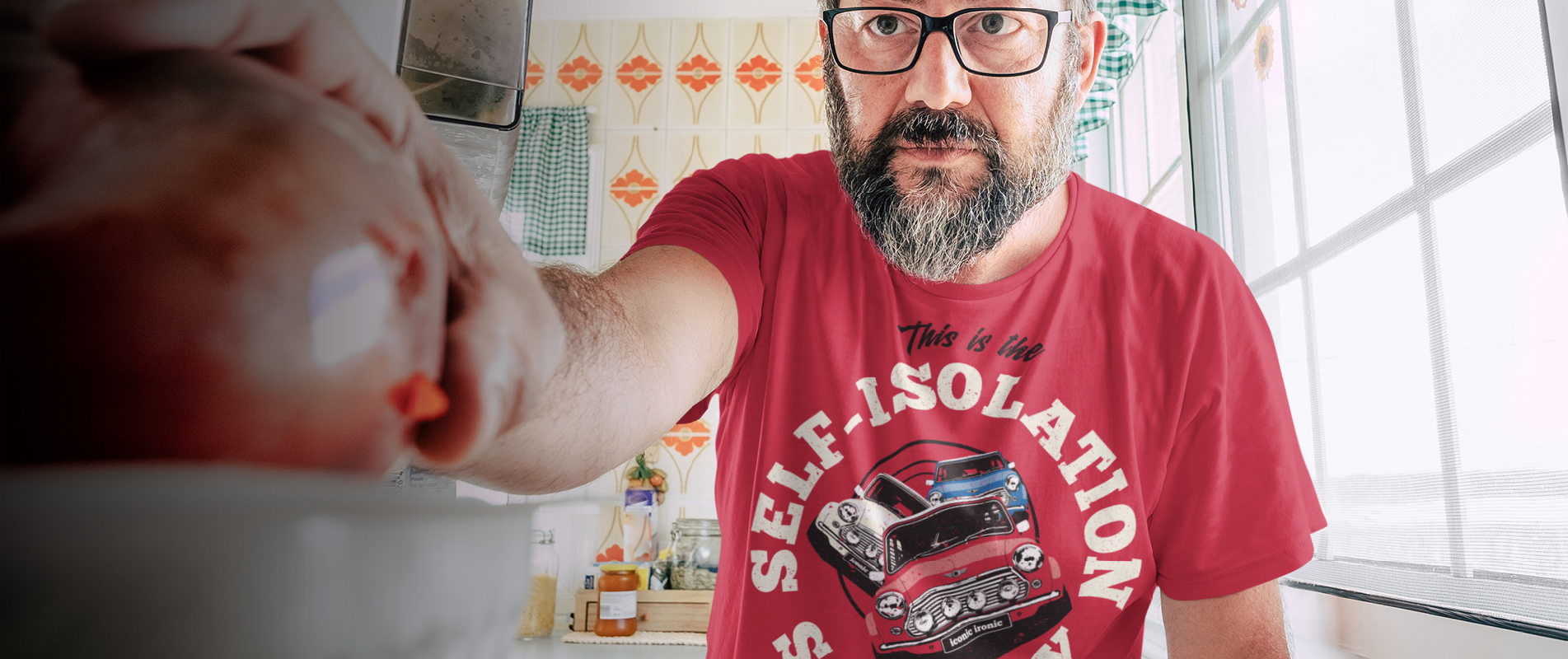 Man in kitchen reaching for snack wearing self isolation t shirt